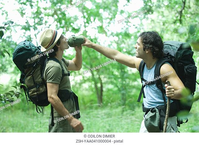 Two hikers, one holding water canteen for other