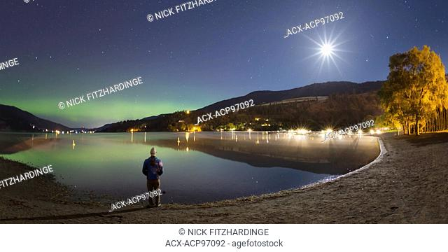 Lone person at night witnessing the Aurora Borealis and moonrise, British Columbia, Canada