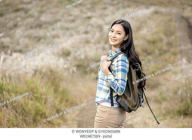 Side view of young smiling woman wearing a backpack staring at front