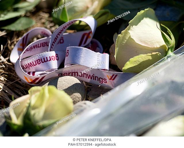 Flowers and a keychain which reads 'Germanwings' are placed around a memorial stele for the victims of Germanwings flight 4U 9525 in La Vernet, France