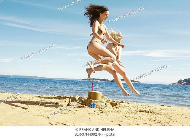 Women jumping over sandcastle