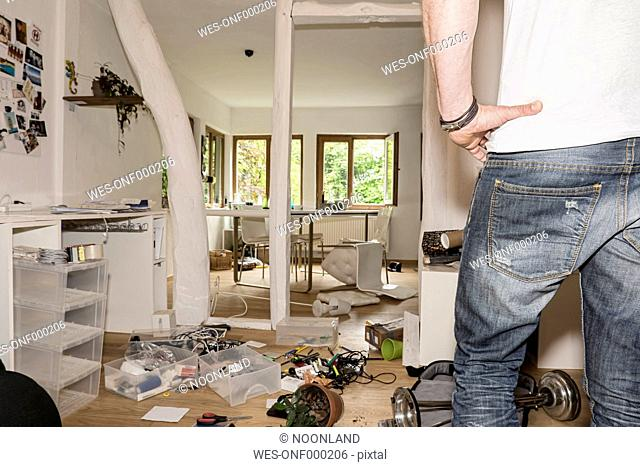 Germany, North Rhine Westphalia, Mature man looking at messy home