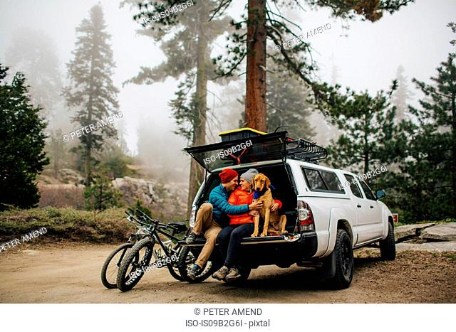 Couple and dog sitting on tailgate of jeep wagon, Sequoia National Park, California, USA