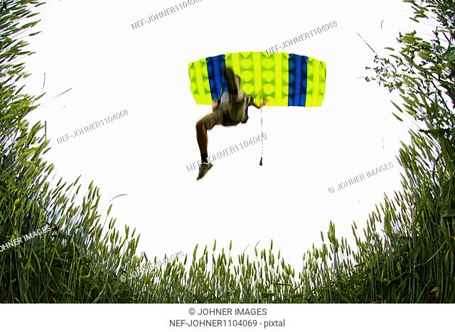 Person with parachute falling, low angle view