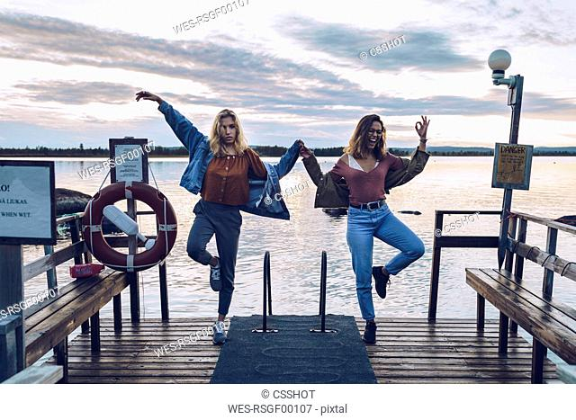 Two girl friends standing on one leg on a pier at Lake INari, Finland