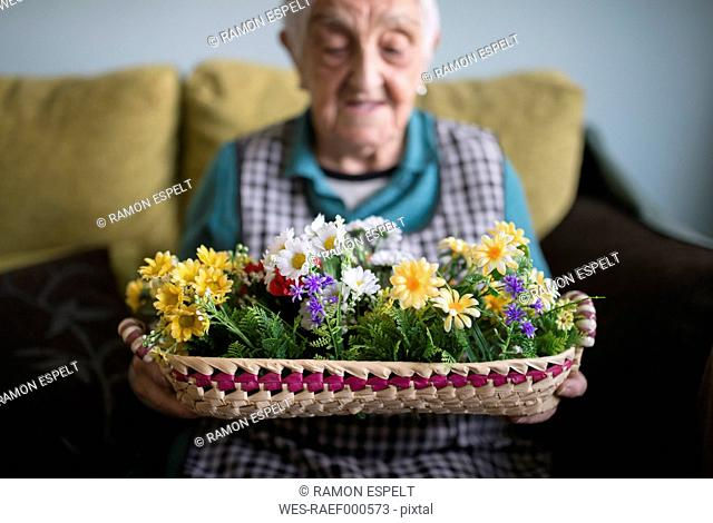 Senior woman showing a basket decorated with artificial flowers