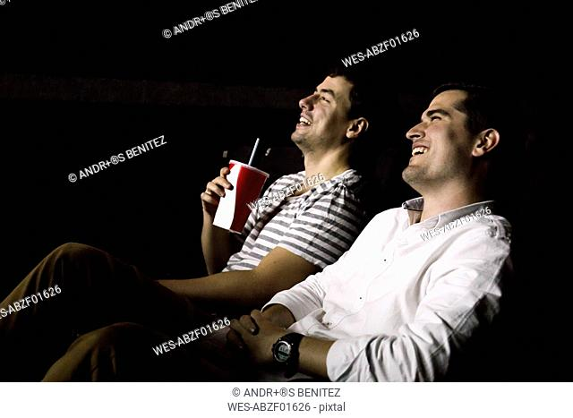 Two men watching a movie in a cinema