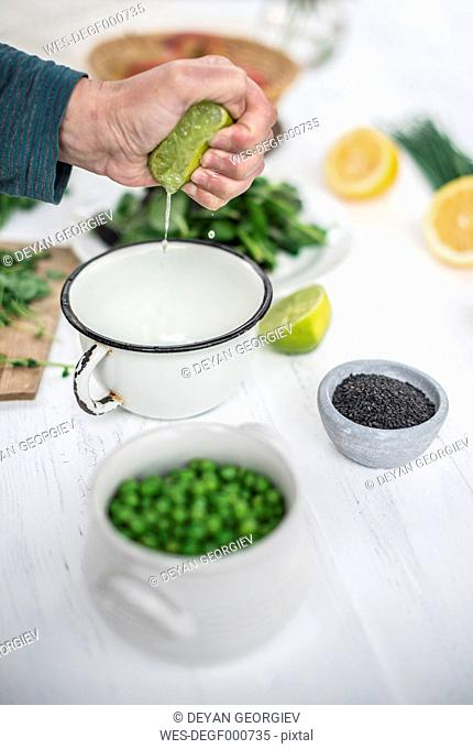 Hand squeezing a lime preparing a salad