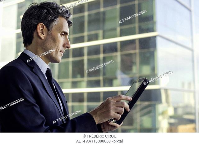 Man with digital tablet by window in high rise building