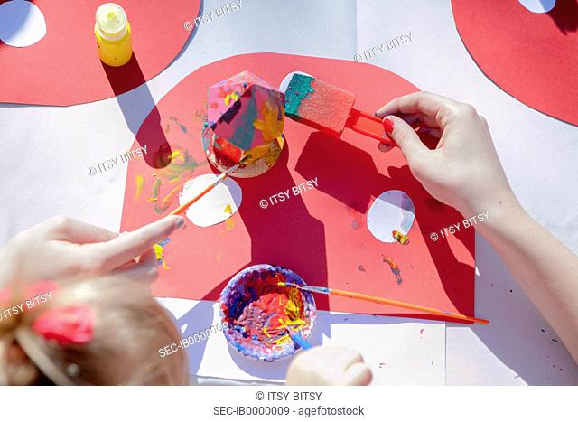Children painting wooden toys outdoors
