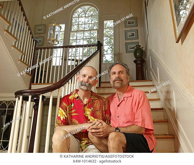 Married same sex gay couple holding hands while sitting on staircase in the grand center hall of their home