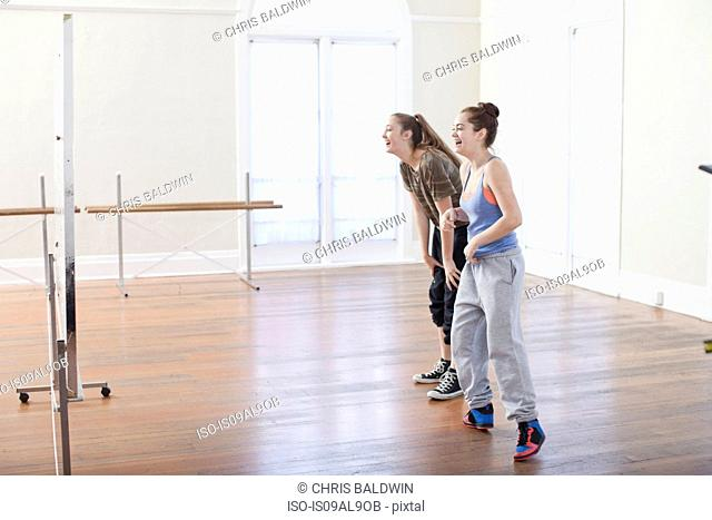 Two teenage girls doing warm up dance in ballet school