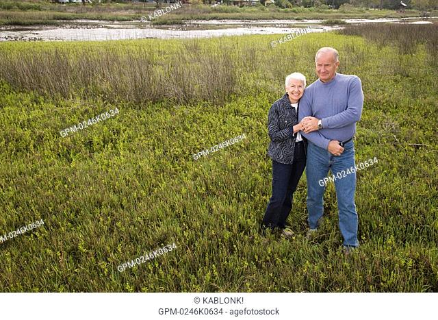Senior couple standing in grassland with arm in arm, high angle view