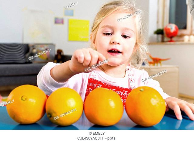 Girl counting oranges on table