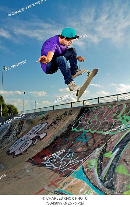 Skateboarder jumping on half pipe