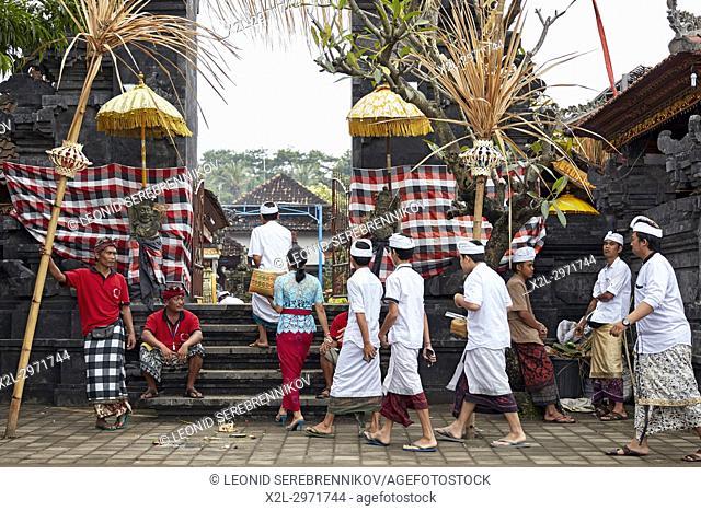 People wearing traditional Balinese clothing go to a local temple near Bugbug village. Karangasem Regency, Bali, Indonesia