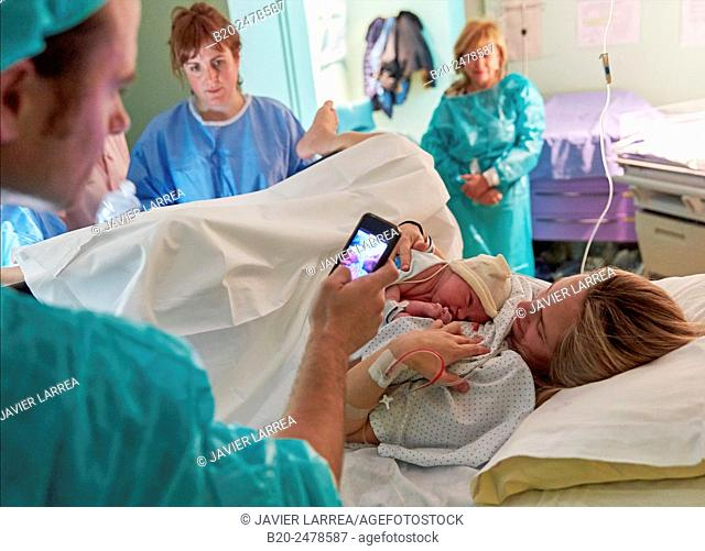 Man taking picture of mother with newborn child in delivery room, Hospital Donostia, San Sebastian, Basque Country, Spain
