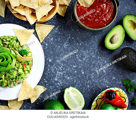Traditional mexican sauces guacamole and salsa with fresh ingredients on stone background
