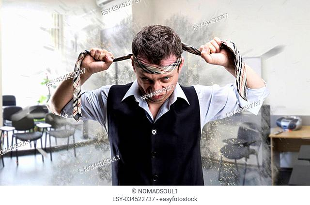 Agressive businessman fighter with a tie on his head in the office
