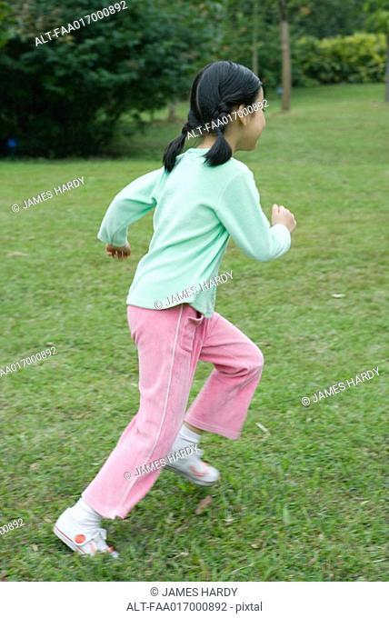 Little girl running across grass