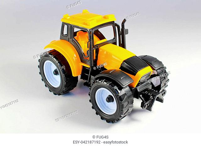 Yellow tractor model, toy isolated on white background