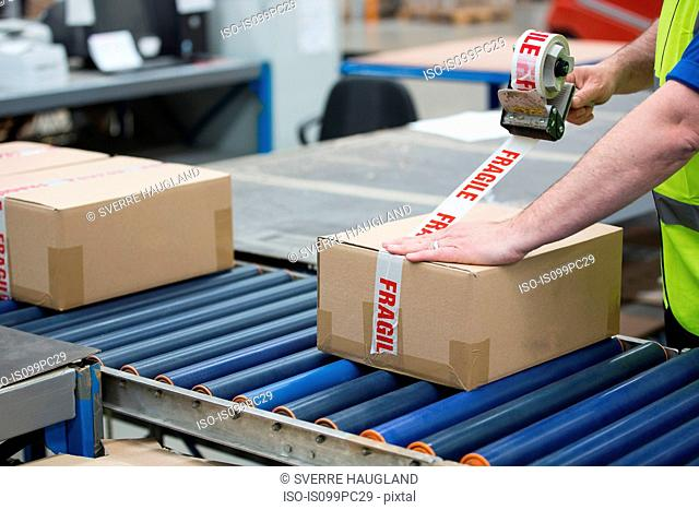 Man packing cardboard box in warehouse