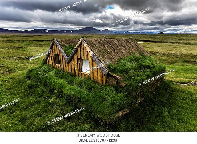 Overgrown sod house in rural landscape