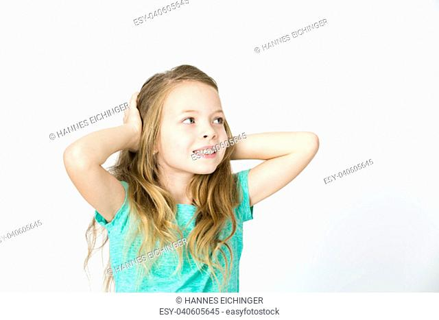 beautiful young blond girl is happy and dancing and posing in the studio in front of white background
