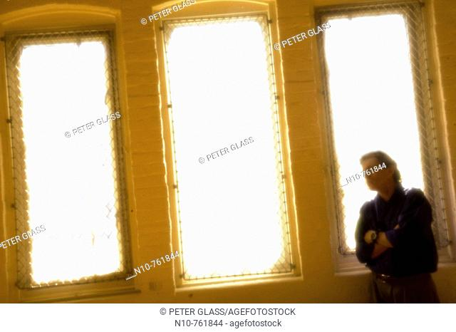 Man standing in front of brightly lit windows