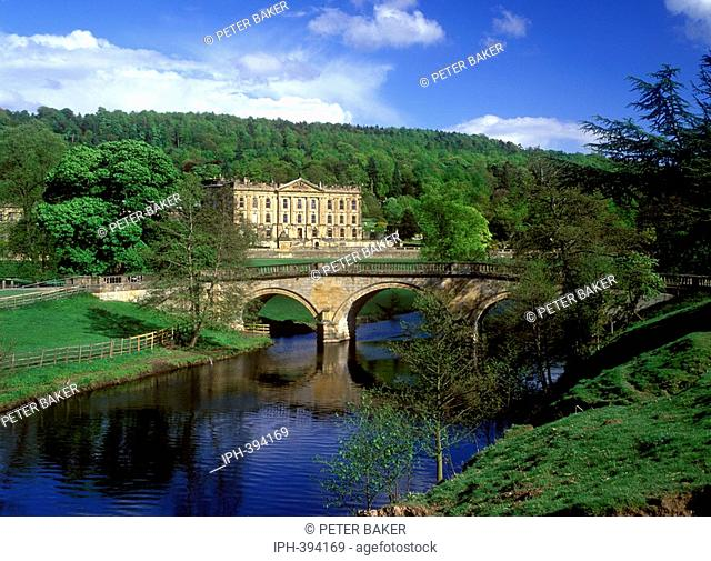 Chatsworth House - View of the large country house reached by a stone arched bridge over the River Derwent