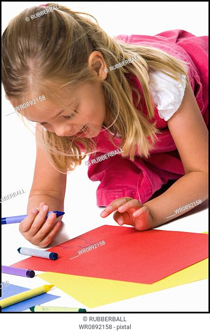 Close-up of a girl drawing on a sheet of paper
