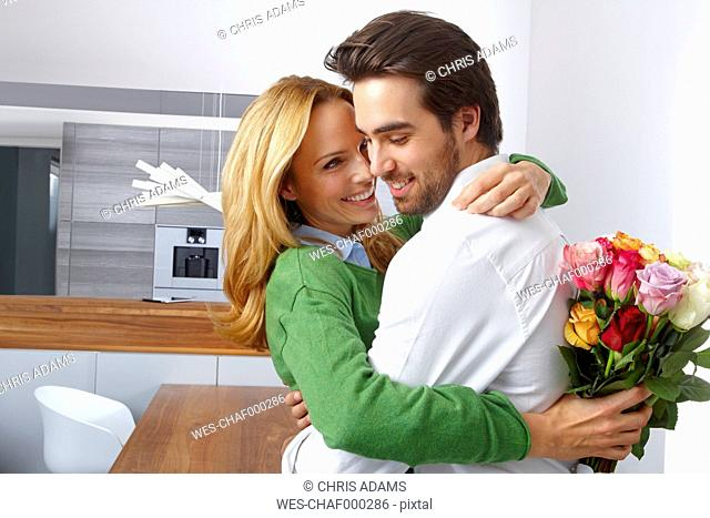 Young woman holding bunch of flowers hugging her boyfriend at home
