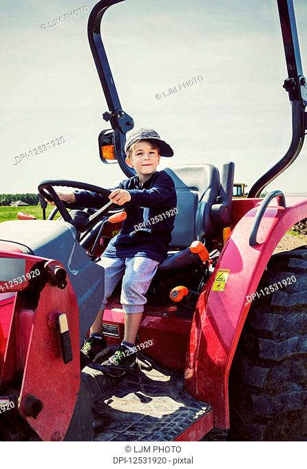 A young boy petending to ride a red tractor on a farm with his hat crooked on his head; Edmonton, Alberta, Canada