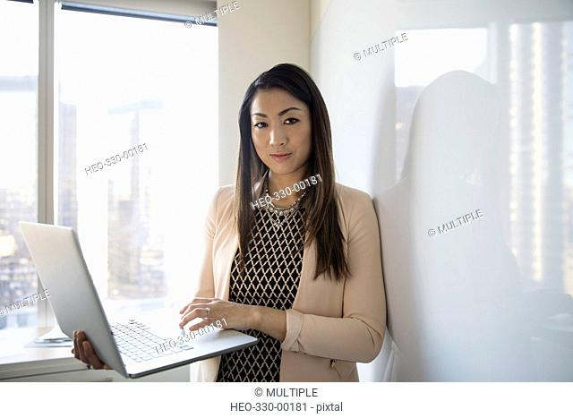 Portrait confident businesswoman using laptop in highrise office