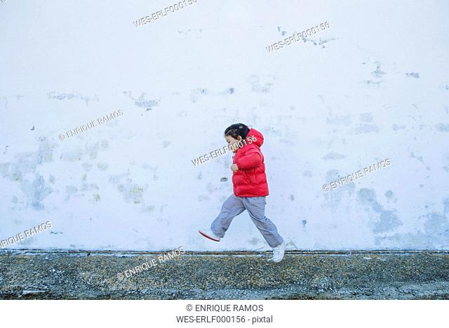 Little girl running in front of a wall