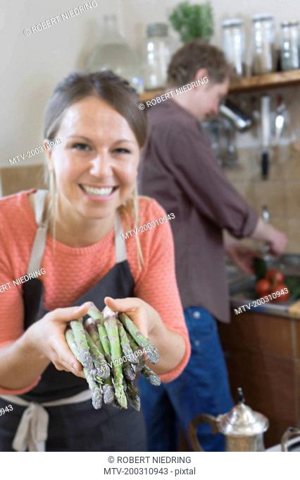 Couple preparing food, woman holding asparagus