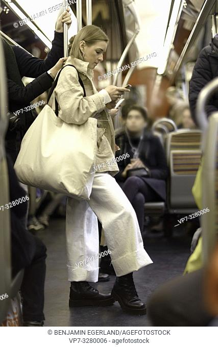 fashionable woman standing in public transportation, looking at phone, in Paris, France
