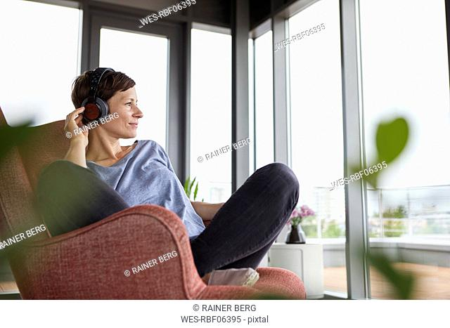 Woman sitting in armchair at home listening to music with headphones