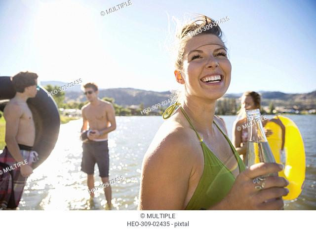 Smiling young woman drinking bottled water at sunny summer lake with friends