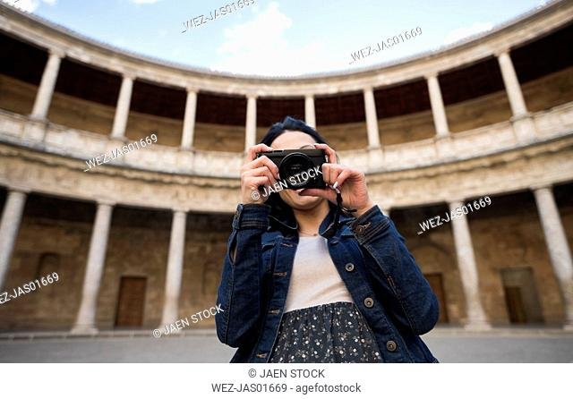 Spain, Granada, young woman taking pictures at the Alhambra