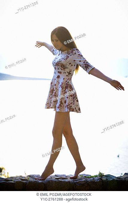 Young woman walking on edge