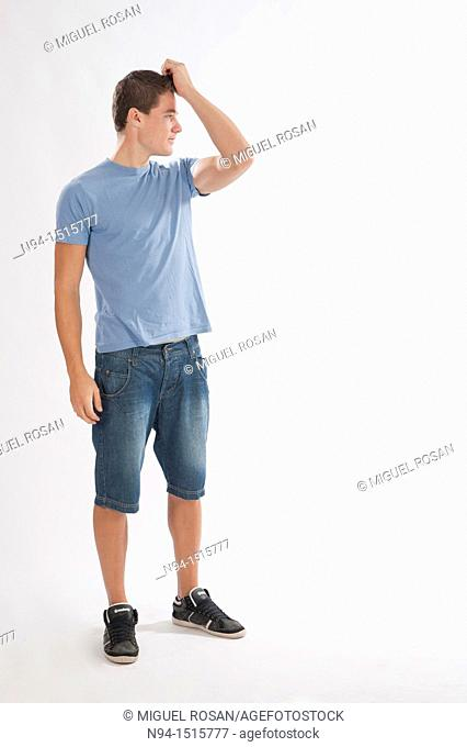 Full-body photograph of a teenage boy standing with hands in hair