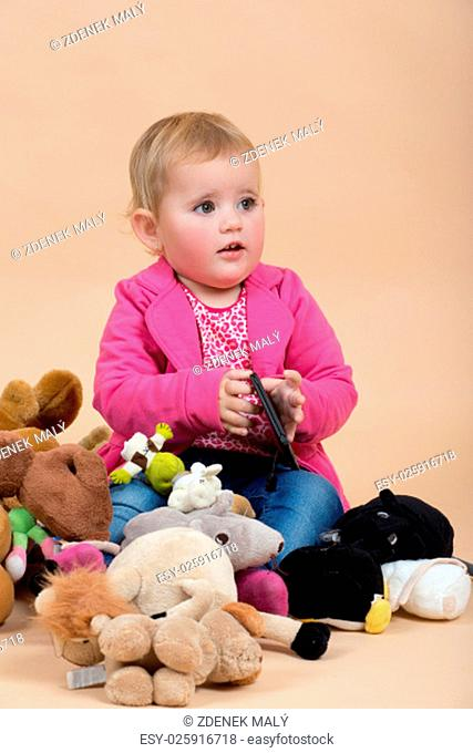 portrait of young cute baby on beige background with plushy toys