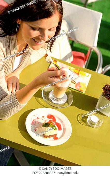 Woman eating cheesecake at cafe bar happy