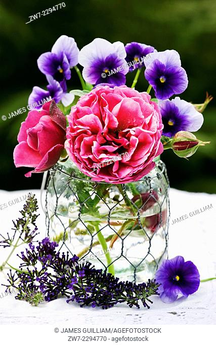 Roses and Viola flowers in glass vase