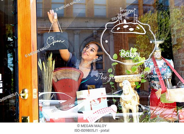 Female worker in bakery, turning sign to open