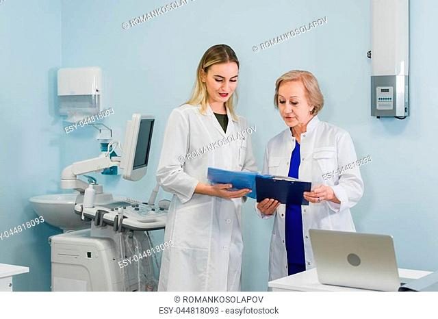 Senior doctor talking with young woman assistant standing in the gynecological office with chair and lamp on the background