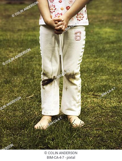 Girl with grass stained pants outdoors