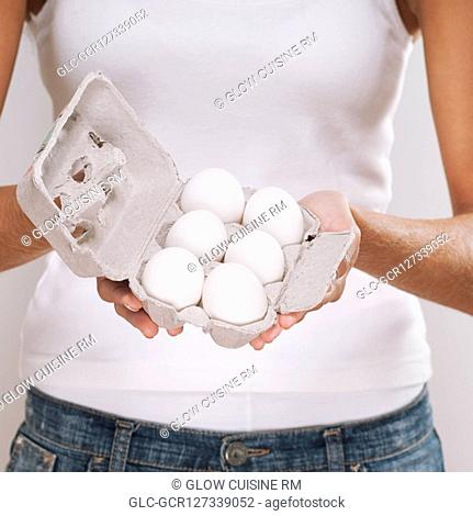 Mid section view of a woman holding a carton of eggs