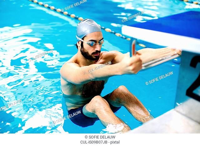 Man in swimming pool holding starting block